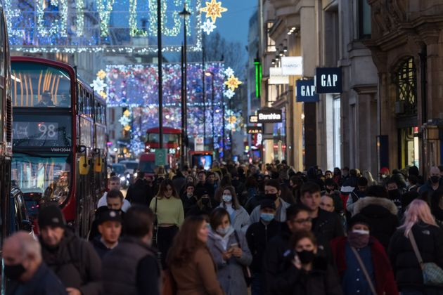 Crowds of shoppers and commuters walk along Oxford Street ahead of introduction of tougher coronavirus...
