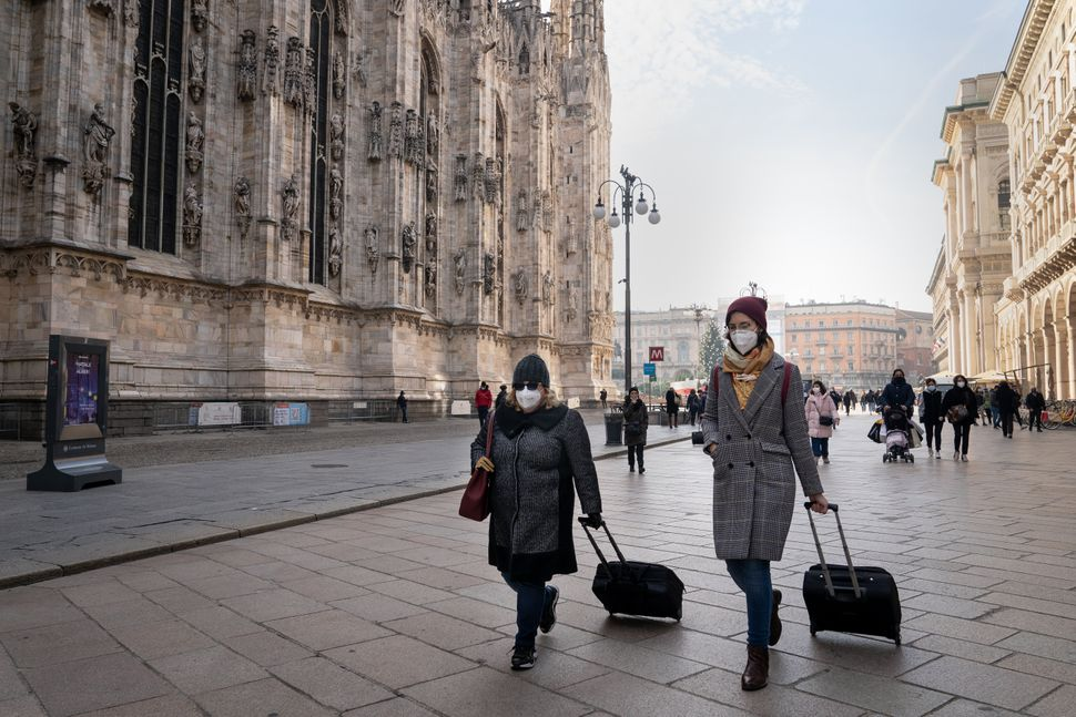 Two people walk in Duomo Square in Milan, Italy, on Dec. 14. The Italian government is expected to announce updated coronavir