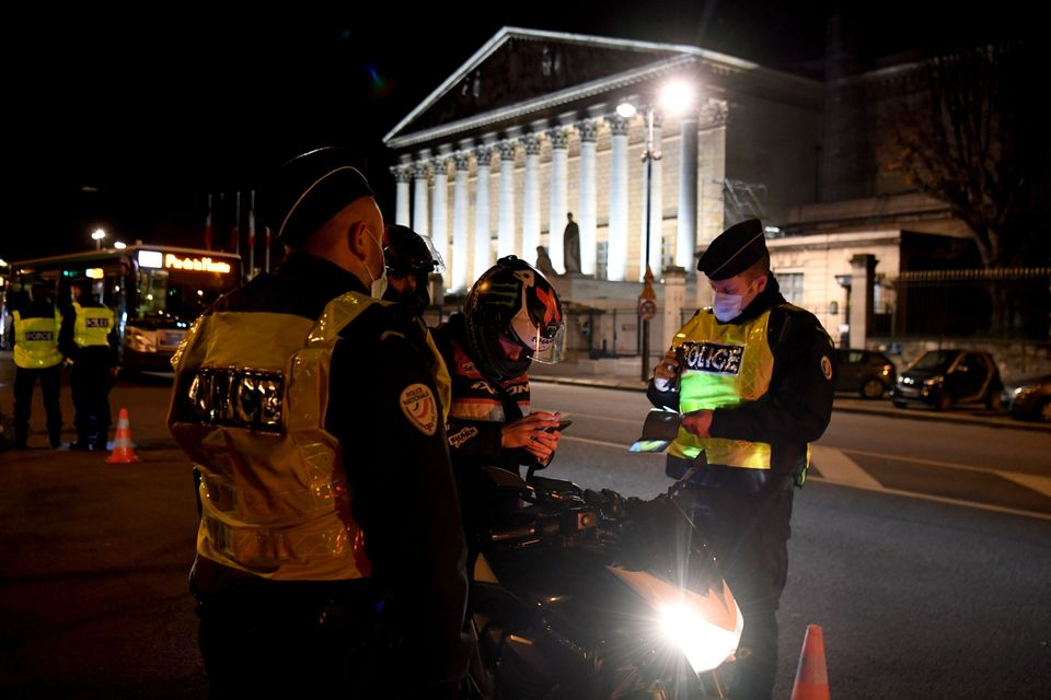 French police check the permission to move of a motorcyclist on December 15, 2020 in Paris, as a new...