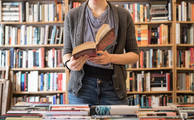 Smiling beautiful young female customer reading book standing against bookshelf at
