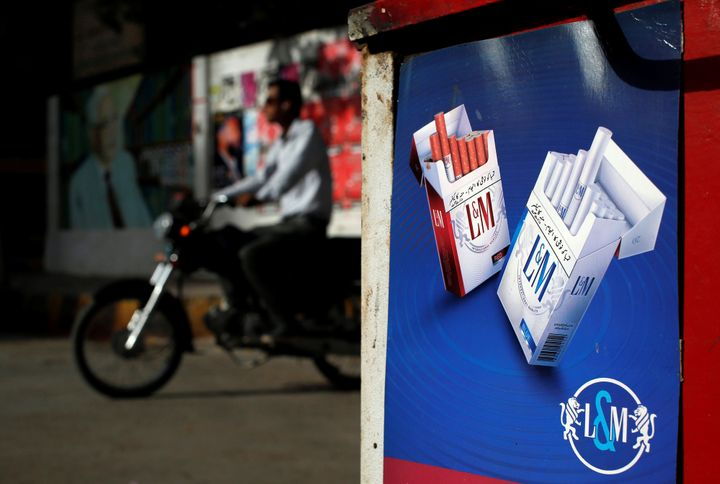 A commuter rides his bike past an advertisement for L&M cigarettes, a Philip MorrisInternational brand, at a kiosk along a road in Karachi, Pakistan in May 2018.