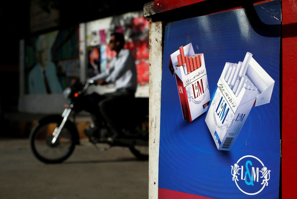 A commuter rides his bike past an advertisement for L&M cigarettes, a Philip Morris brand, at a kiosk along a road in Kar