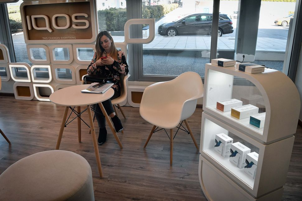 A woman sits in an IQOS lounge at the Papastratos tobbacco company facilities in Aspropyrgos, Greece. Philip Morris Internati