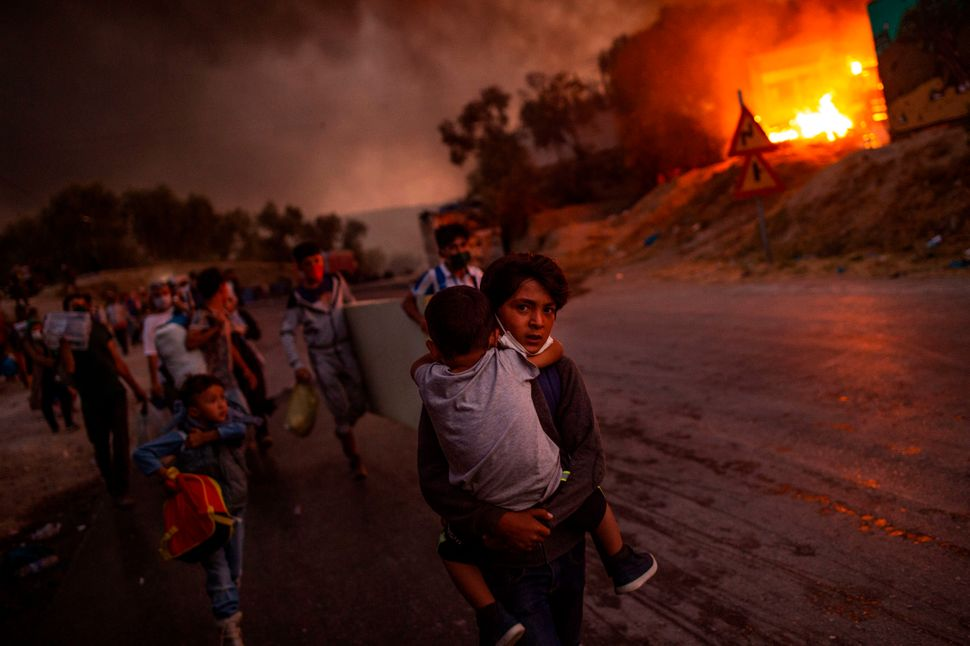 Thousands of asylum-seekers on the Greek island of Lesbos flee for their lives on Sept. 9 as a huge fire rips through the cam