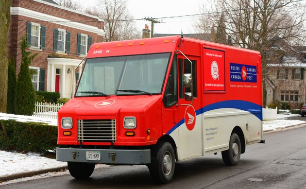 Toronto, Ontario, Canada - December 1, 2013: view of Canada Post vehicles standing in Forest hill, Toronto,