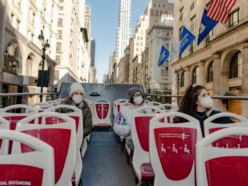 A family from Texas visiting New York and taking a tour on a double decker bus going down 5th Avenue, Manhattan on November 24, 2020