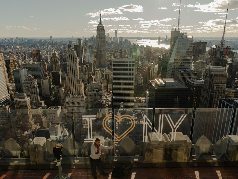"""A man posing in front of the """"I Heart NY"""" sign at the observation deck at the Top of the Rock at Rockefeller Center in midtown Manhattan."""