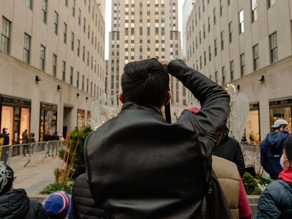 A man takes a photo of the Christmas tree at Rockefeller Center in midtown Manhattan.