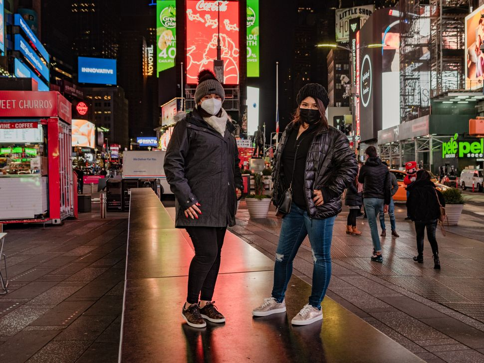 """Daisy Martinez and Cindy Herrera are seen here on their first night in New York, shortly after arriving and checking into their hotel on Times Square. They decided to travel at this time to take advantage of empty streets. """"We are afraid of coronavirus, but we're taking maximum precautions with masks, sanitizing, washing hands, and that's about all we can do."""""""