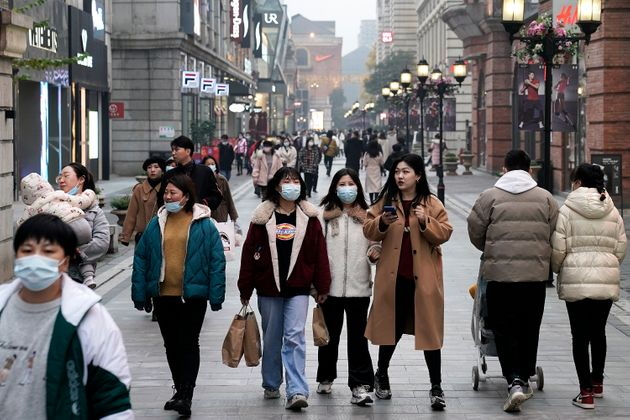 WUHAN, CHINA - DECEMBER 08: (CHINA OUT) Residents are seen wearing a mask as they walk through a street...