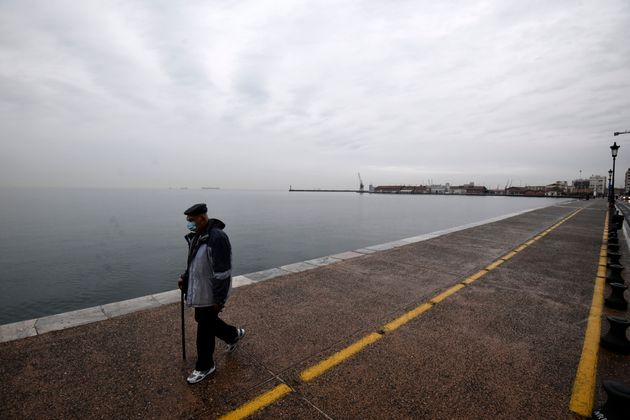 A pedestrian wearing a face mask against the spread of the coronavirus, walks on a coastal avenue during...