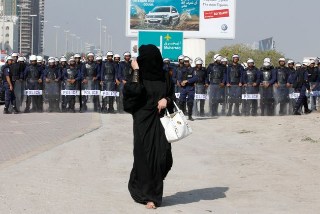 An anti-government protester wearing an abaya walks in front of riot police as she arrives to participate...