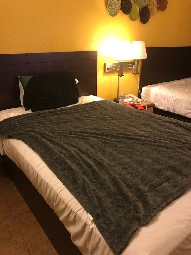 The Hotel COVIDfornia bed with the super-comfy blanket the author brought with