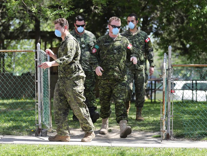Military personnel are seen changing shifts behind the Eatonville Care Centre in Toronto on May 26, 2020.