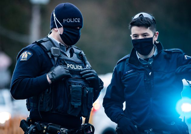 RCMP officers wearing face masks to curb the spread of COVID-19 stand by as protesters opposed to the...