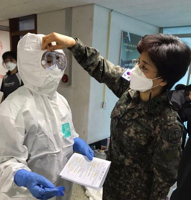 간호사관생도가 개인보호구 착용 후 교수의 평가를 받는