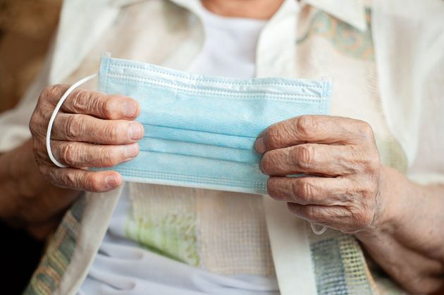 The old woman holds a medical mask in hands, preparing to wear it to protect herself from Coronavirus...