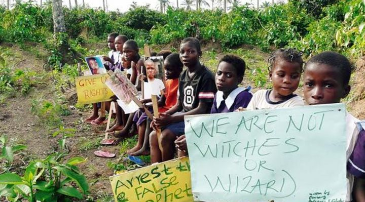 """Children in Nigeria pose with signs opposing the labelling of them as """"witches and wizards"""". There has been a disturbing rise in abuse of children associated with witchcraft and experts fear coronavirus will make things much worse for the vulnerable"""