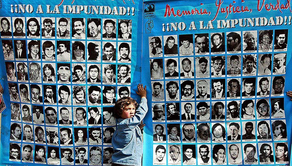 Santiago de Chile, 2004. Un niño sostiene un cartel con las fotos de algunos de los desaparecidos...
