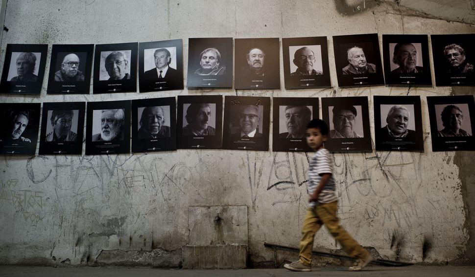 Santiago de Chile, 2015. Un niño camina junto a una muestra de fotografías en una galería...