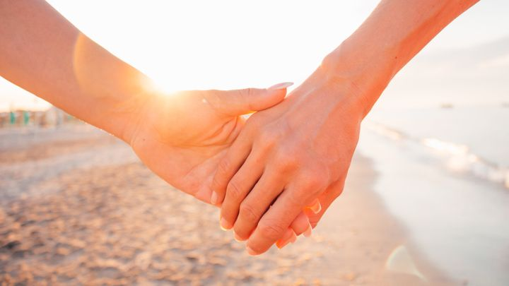 Close-up of two female holding hands against sunset - two girls walking on the beach hand by hand - same-sex lesbian couple and female friendship concepts