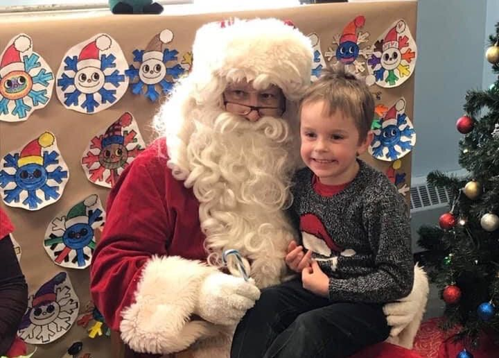 The writer's son sits with an unnamed actor portraying Santa Claus.