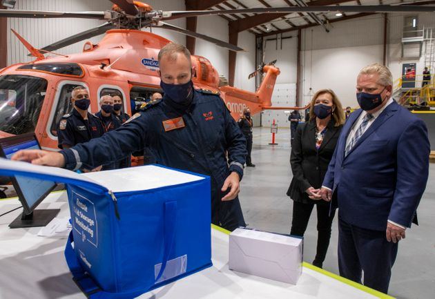 ORNGE Chief Paramedic Justin Smith, left, demonstrates a Remote Cold Storage Monitoring insulated container...