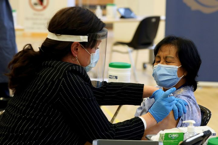 A healthcare worker administers the first dose of the Pfizer and BioNTech COVID-19 vaccine in Ontario to personal support worker Anita Quidangen at The Michener Institute in Toronto on Dec. 14, 2020.