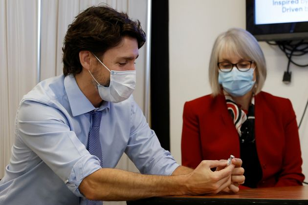 Prime Minister Justin Trudeau. with Health Minister Patty Hajdu, holds an empty COVID-19 vaccine vial...