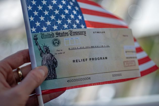 COVID-19 economic Stimulus check in female hand on blurred USA flag background. Relief program