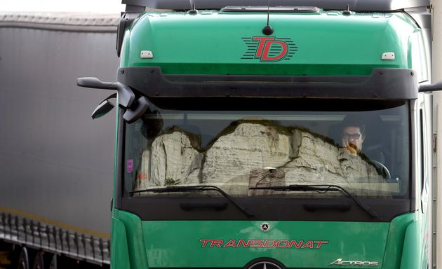 The White Cliffs are reflected in the windscreen of a lorry whilst the driver sits his cab and queues...
