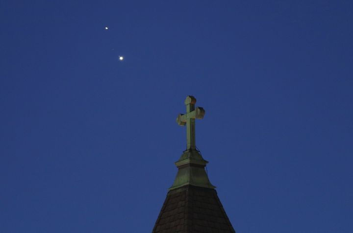 Saturn and Jupiter set behind a church ahead of their conjunction that is being called The Christmas Star next week on December 18, 2020 in Jersey City, New Jersey.
