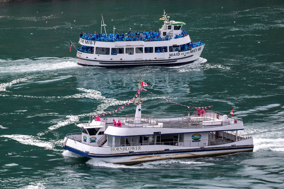 American tourist boat Maid of the Mist, limited to 50% occupancy under New York State rules, glides past a Canadian vessel li