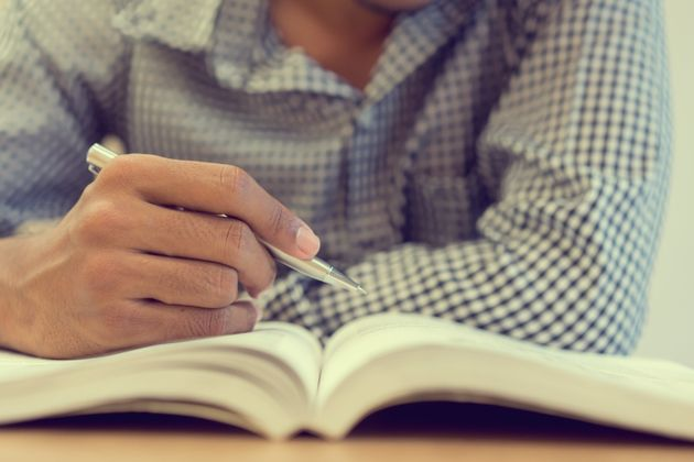 close up student man hand holding pen for guideline reading on text book at campus library for examination...