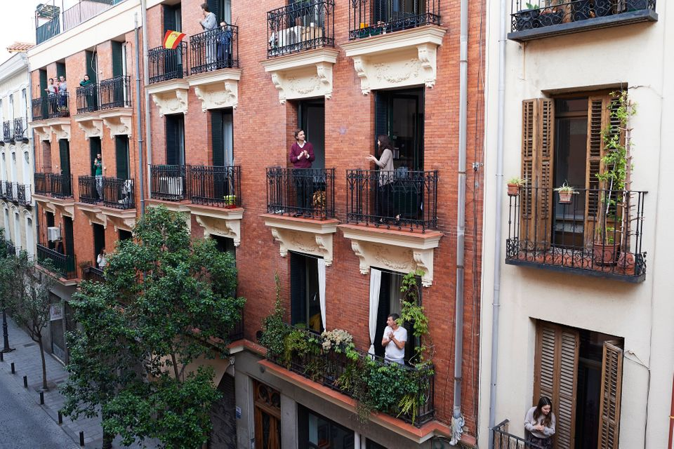 People on their balconies applaud to pay tribute to health care workers fighting against the coronavirus...