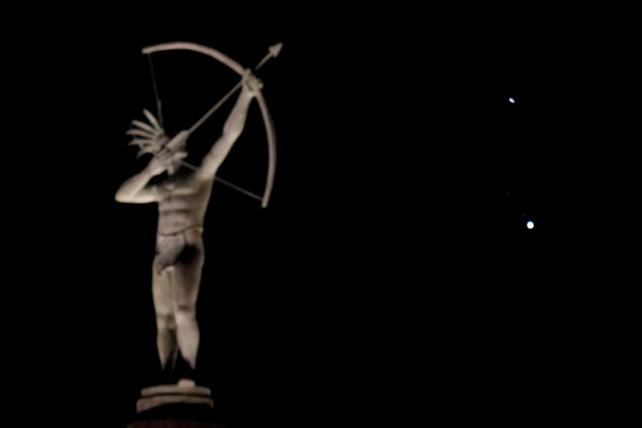 A statue of a Kansa Indian atop the Kansas Statehouse stands in the foreground as Saturn, top, and Jupiter, below, are seen Saturday, Dec. 19, 2020 in Topeka, Kansas.