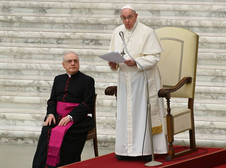 Pope Francis, flanked by Monsignor Leonardo Sapienza, delivers his Christmas greetings to the employees of the Vatican on Monday.