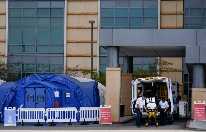 Medical workers remove a stretcher from an ambulance near medical tents outside the emergency room at UCI Medical Center, in