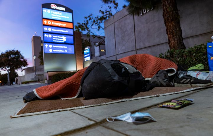 A homeless person sleeps outside the Los Angeles County + USC Medical Center hospital entrance in Los Angeles on Wednesday. H