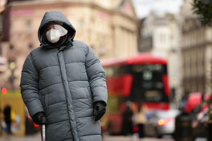 A man wearing a face mask and face shield waits at a pedestrian crossing on Regent Street in London, England, on Dec. 21, 2020.