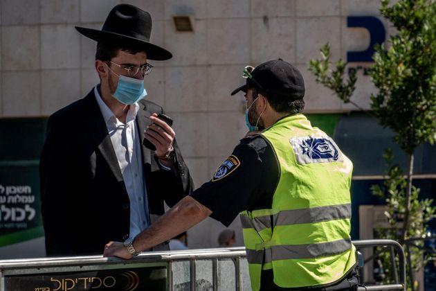 Un policía de Israel junto a un hombre durante la pandemia de