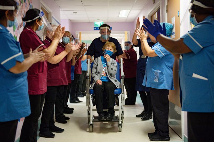 Margaret Keenan, 90, receives applause from staff as she returns to her ward after becoming the first patient in the world to receive the Pfizer-BioNTech COVID-19 vaccine at University Hospital in Coventry, England, on Dec. 8.