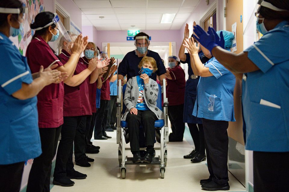 Margaret Keenan, 90, receives applause from staff as she returns to her ward after becoming the first...