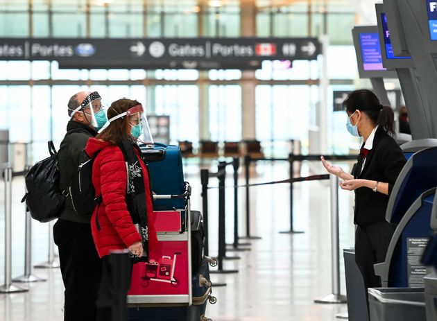 People wear protective equipment as they check in at Pearson International Airport during the COVID-19...