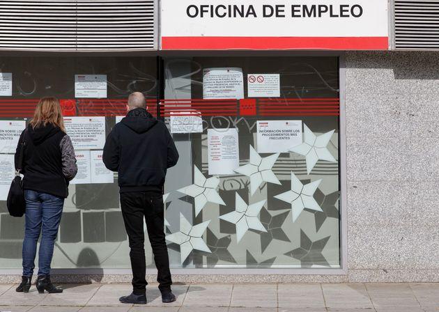Dos personas leen los carteles en la puerta de una oficina de