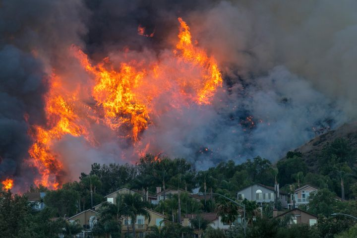 Flames rise near homes during the Blue Ridge fire on Oct. 27 in Chino Hills, California.