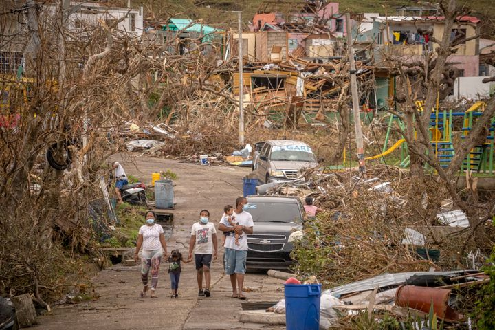 A family walks amid destruction on Nov. 22 in Providencia, Colombia, which was hit by Hurricane Iota as a Category 5 storm, t