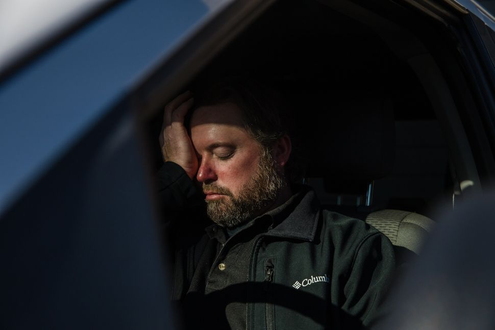 Mike Kurtz sits in his truck to decompress for a few minutes after working more than 10