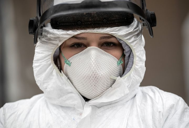 Nurse Hannah Sutherland, dressed in personal protective equipment, awaits new patients at a drive-thru coronavirus testing st