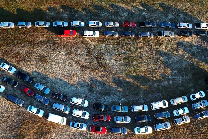 People line up in their cars to receive food assistance at the Share Your Christmas food distribution event on Dec. 9, 2020, in Groveland, Florida. Central Florida food banks struggled to serve those facing food insecurity during the holiday season amid the COVID-19 pandemic.